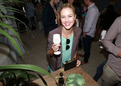 Guest smiling holding drink Brown Brothers Summer of Prosecco Pop-Up Beach Bar