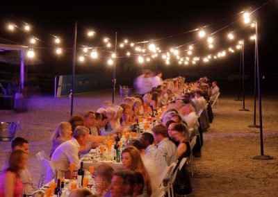 Guests sitting at table outside night time Cable Beach Broome Polo Tournament