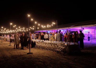 Guests standing talking outside night time Cable Beach Broome Polo Tournament