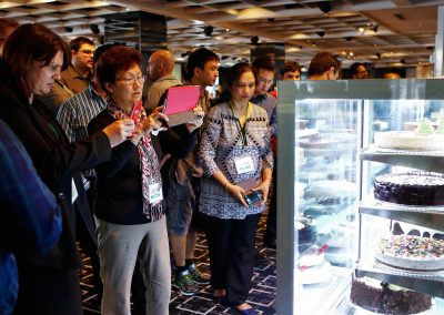 Guests admiring taking photos of cakes Cheesecake Shop Franchise Conference