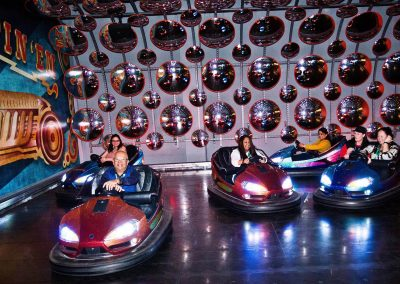 Guests having fun driving dodgem cars at the Cheesecake Shop Franchise Conference