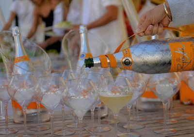 Champagn bottle pouring in glass Clicquot Beach House