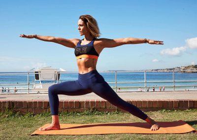 Female yoga teacher outdoors ocean background Clicquot Beach Hut at Bondi Beach event