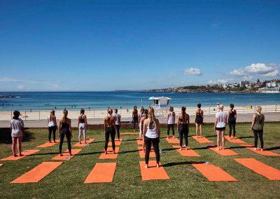 Group people yoga outdoors Clicquot Beach Hut at Bondi Beach event
