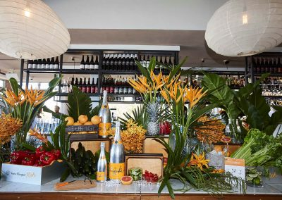 Champagne bottles display with flowers fruit vegetables Clicquot Beach Hut at Bondi Beach event