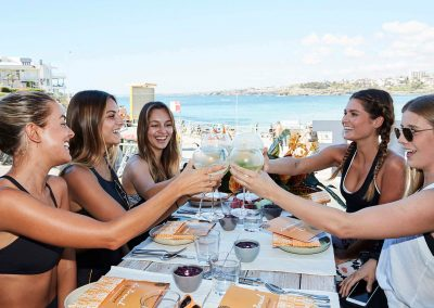 5 models sitting at table holding drinks Clicquot Beach Hut at Bondi Beach event