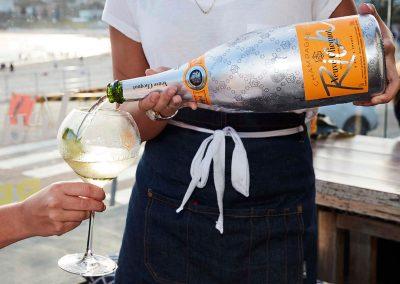 Close up waiter pouring champagne in glass Clicquot Beach Hut at Bondi Beach event
