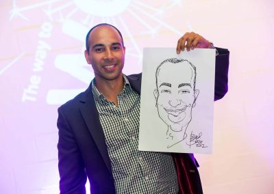Guest smiling holding caricature drawing Credit Union Australia National Business Strategy