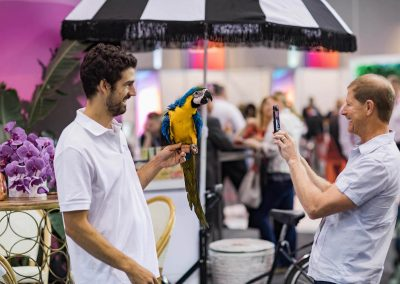 Man holding parrot guest taking picture Dual Australia Exhibition Stand - Miami Poolside
