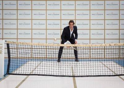 Roger Federer holding tennis racket at Moet event