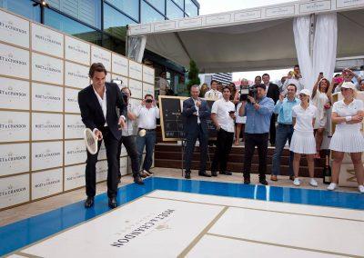Roger holding racket at mini tennis court Game, Set & Moet with Roger Federer