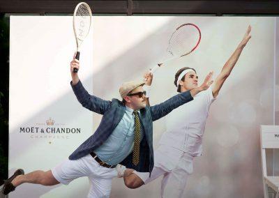 Guest copying Roger Federer serve image in background at Moet et Chandon event