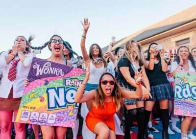 Groupf of women laughing holding Wonka Rainbow Nerds signs Google Summer Party event