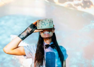 Smiling woman looking in VR headset Google Summer Party event