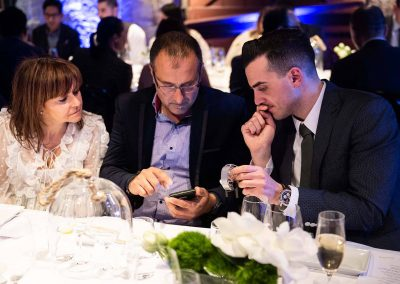 3 guests looking at phone at Gregory Jewellers & Breitling VIP client dinner