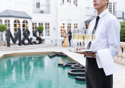 Waiter holding tray drinks outside pool Marks & Spencer Australian Online Store launch