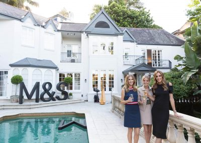 Kate Waterhouse, Nadia Fairfax and Rebecca Judd holding glasses next to swimming pool Marks & Spencer Australian Online Store launch