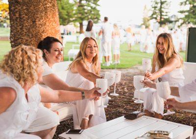 Female guests holding goblets toasting Moet Dinner en Blanc National Sponsorship Activation