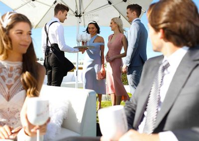 Waiter serving guests at Moet et Chandon Lawn at Melbourne Racing Club
