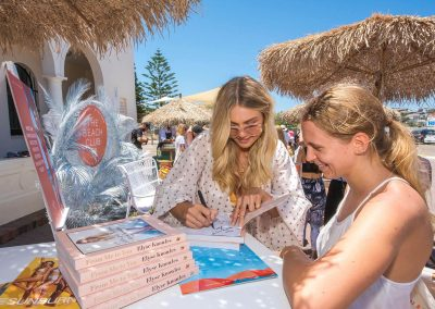 Elyse Knowles autographing book at the Seafolly Beach Club launch