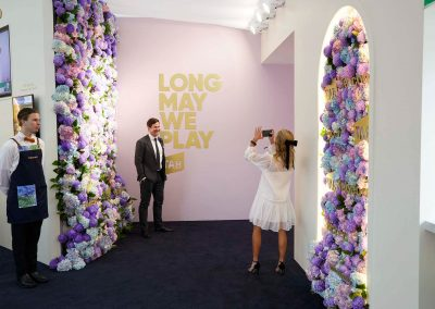 Guest taking photos in front of the Tabcorp floral wall