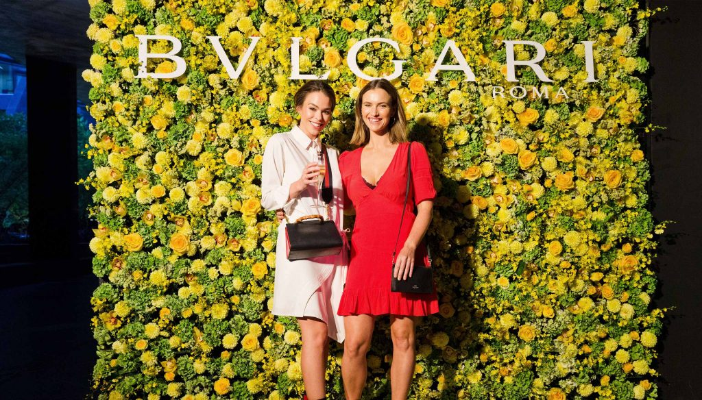 Guests in front of Bulgari floral wall