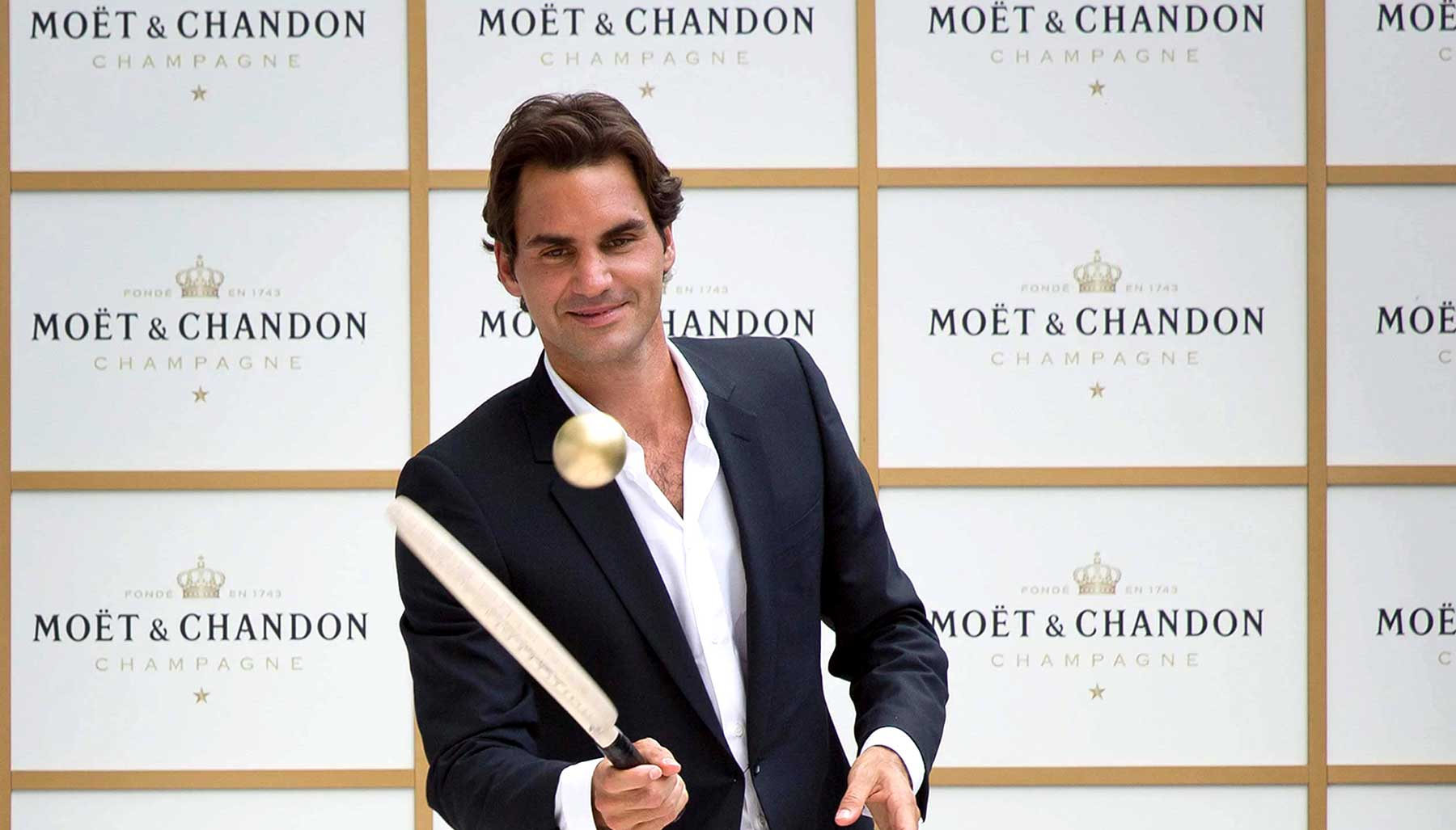 Roger Federer with racquet and gold tennis ball at Moet et Chandon event in his honour